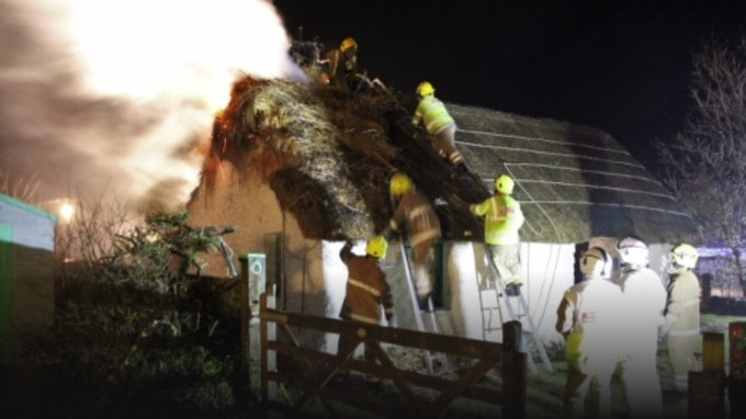 Fire in the thatch at Cruck Cottage.