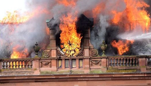 The flames engulf the building's clock
