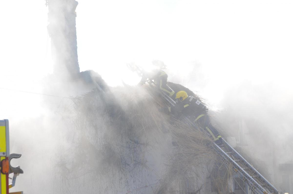 Smoke billows out of the thatch