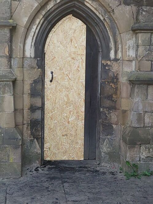 The heavy wooden door to All Saints Church, in Highcross Street, Leicester, was badly damaged in the fire, but not breached