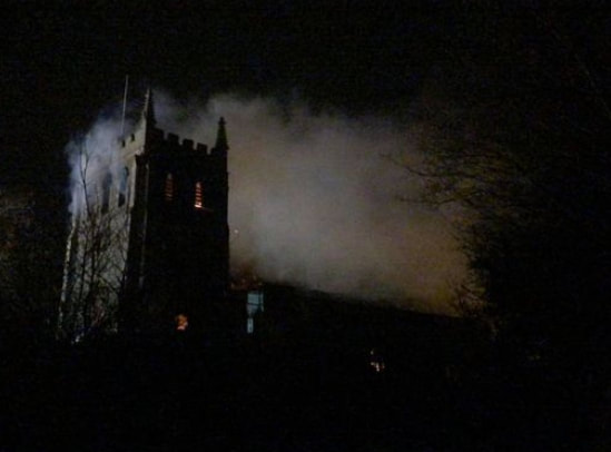Smoke continues to pour out of the church in the darkness