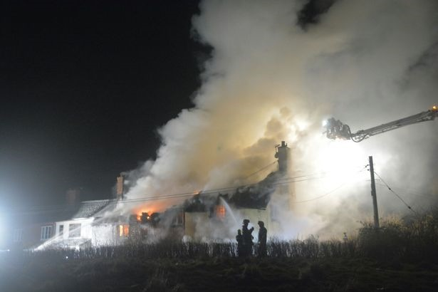 Fire devastates the two Grade II houses in Sowton, Devon.