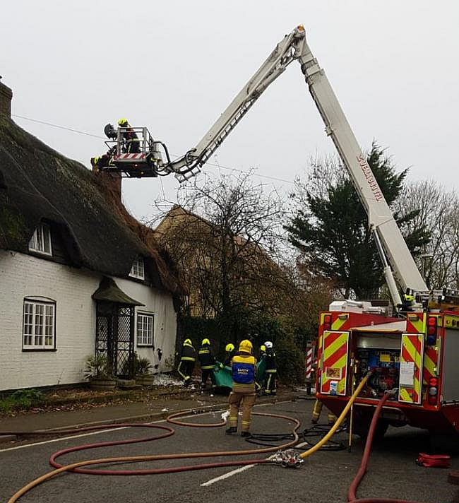 Firefighters try hard to prevent the fire spreading through the thatch of the historic building