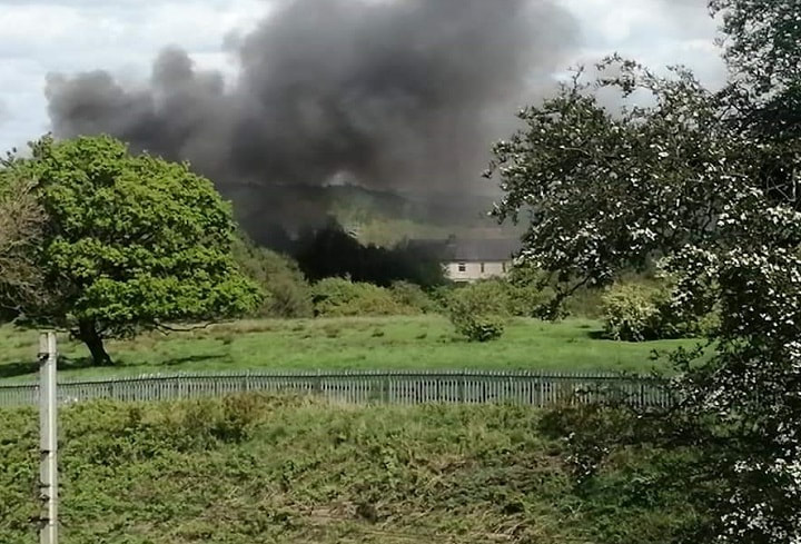 A plume of smoke rises from the old mill site